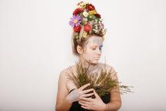 有花的一个少妇在她的头和手 与花的春天图象 有一棵五颜六色的植物的人 女孩和开花 库存照片