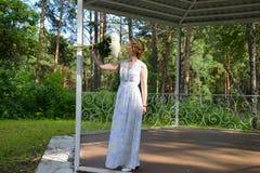 有花的一个愉快的女孩在森林树荫处站立 免版税图库摄影