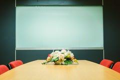 有花的会议室在桌上 免版税库存照片