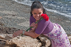 有花的俏丽的妇女在海滩 库存图片