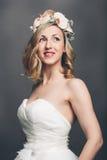 有花的典雅的俏丽的新娘在她的头发 免版税库存图片