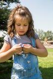 有花的可爱的儿童女孩 夏天绿色自然 库存照片
