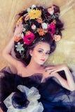 有花的可爱的妇女在她的在金黄背景的头发 库存图片