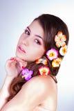 有花的可爱的少妇在头发 免版税库存照片