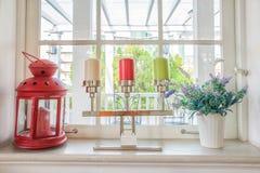 有花的在窗台乡间别墅的花瓶和蜡烛 免版税图库摄影