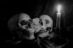 有花的头骨和蜡烛在木桌上点燃有在夜间的黑背景在黑白/静物画st 库存图片