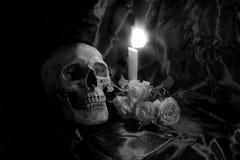 有花的头骨和蜡烛在木桌上点燃有在夜间的黑背景在黑白/静物画st 库存照片