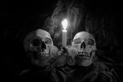 有花的头骨和蜡烛在木桌上点燃有在夜间的黑背景在黑白/静物画st 免版税库存图片
