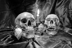 有花的头骨和蜡烛在木桌上点燃有在夜间的黑背景在黑白/静物画st 免版税库存照片