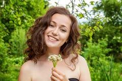 有花的女孩在她的手上在公园 库存照片