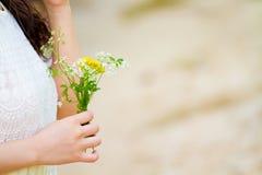 有花的女孩在她的手上 免版税库存图片