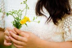 有花的女孩在她的手上 免版税库存照片
