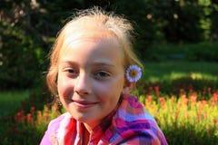有花的女孩在她的头发 免版税库存照片
