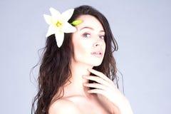 有花的妇女在接触她的脖子的卷发 秀丽,脸面护理,温泉 免版税库存图片