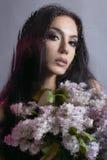 有花的妇女在湿窗口后 库存图片