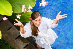 有花的妇女在热带游泳池边 免版税库存照片