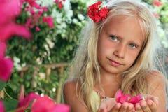 有花的小女孩在她的手上 免版税图库摄影