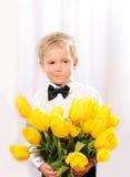 有花的小白肤金发的男孩 免版税图库摄影