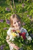 有花的小逗人喜爱的女孩在庭院里 免版税库存图片