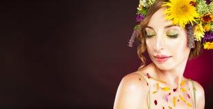 有花的少妇在她的头发和瓣在身体 免版税图库摄影