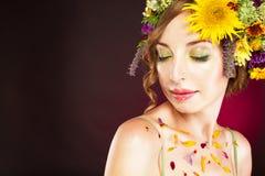 有花的少妇在她的头发和瓣在身体 图库摄影