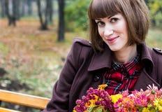 有花的少妇在秋天公园 免版税库存图片