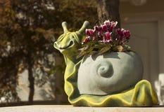有花的庭院罐以蜗牛的形式 免版税库存照片