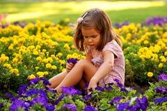 有花的愉快的美丽的小女孩。 图库摄影