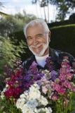 有花的愉快的老人在庭院里 库存照片