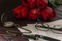 有花的手表在桌上 免版税库存照片
