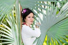 有花的晒日光浴可爱的妇女在棕榈下的长的头发在热带海滩 免版税库存照片
