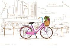 有花的桃红色减速火箭的自行车在城市剪影 库存照片