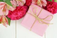 有花的桃红色礼物盒在白色木头 免版税库存图片