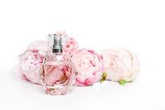 有花的桃红色香水瓶在轻的背景 香料厂,化妆用品,芬芳汇集 免版税图库摄影