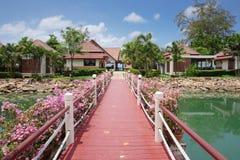 有花的桥梁横跨海湾在一个热带庭院里 免版税库存照片