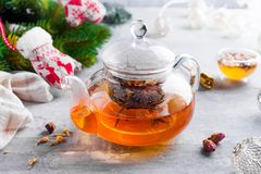 有花的玻璃茶壶栓了茶、热的茶在玻璃茶壶和蜂蜜用金属蜂蜜棍子在石背景 库存照片