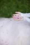 有花的瓣的新娘手 免版税库存图片