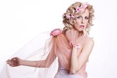 有花的白肤金发的美丽的妇女 免版税库存图片