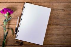 有花的空白的笔记本在木桌上 库存照片
