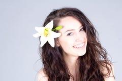 有花的笑的妇女在有微笑的卷发与牙 7温泉 免版税库存图片