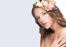 有花的美丽的女孩在她的头发和桃红色构成 春天图象 秀丽表面 库存图片