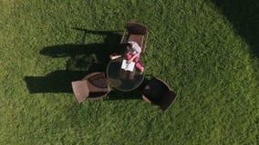 有花的美丽的女孩在绿色草坪放松并且读书 影视素材