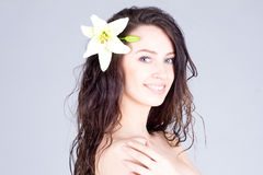 有花的美丽的妇女在有微笑的卷发与牙 秀丽,脸面护理,温泉 免版税图库摄影