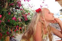 有花的美丽的小女孩在她的头发 免版税图库摄影