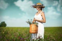 有花的美丽的少妇在领域 库存图片