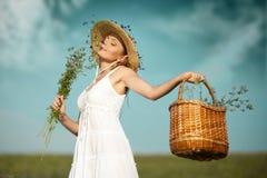 有花的美丽的少妇在领域 免版税图库摄影