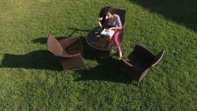 有花的美丽的浅黑肤色的男人在绿色草坪读了书 影视素材