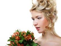 有花的美丽的白肤金发的女孩在白色背景 免版税库存照片