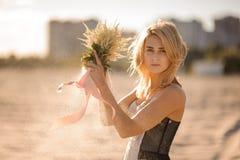 有花的美丽的白肤金发的妇女在手上 库存照片