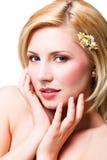 有花的美丽的白肤金发的微笑的妇女在头发 库存图片